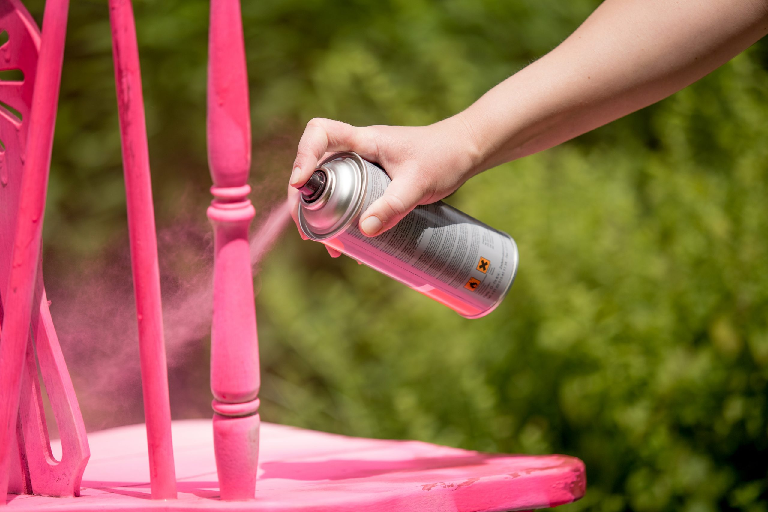 A chair being sprayed with pink spray paint. How to paint metal chairs.