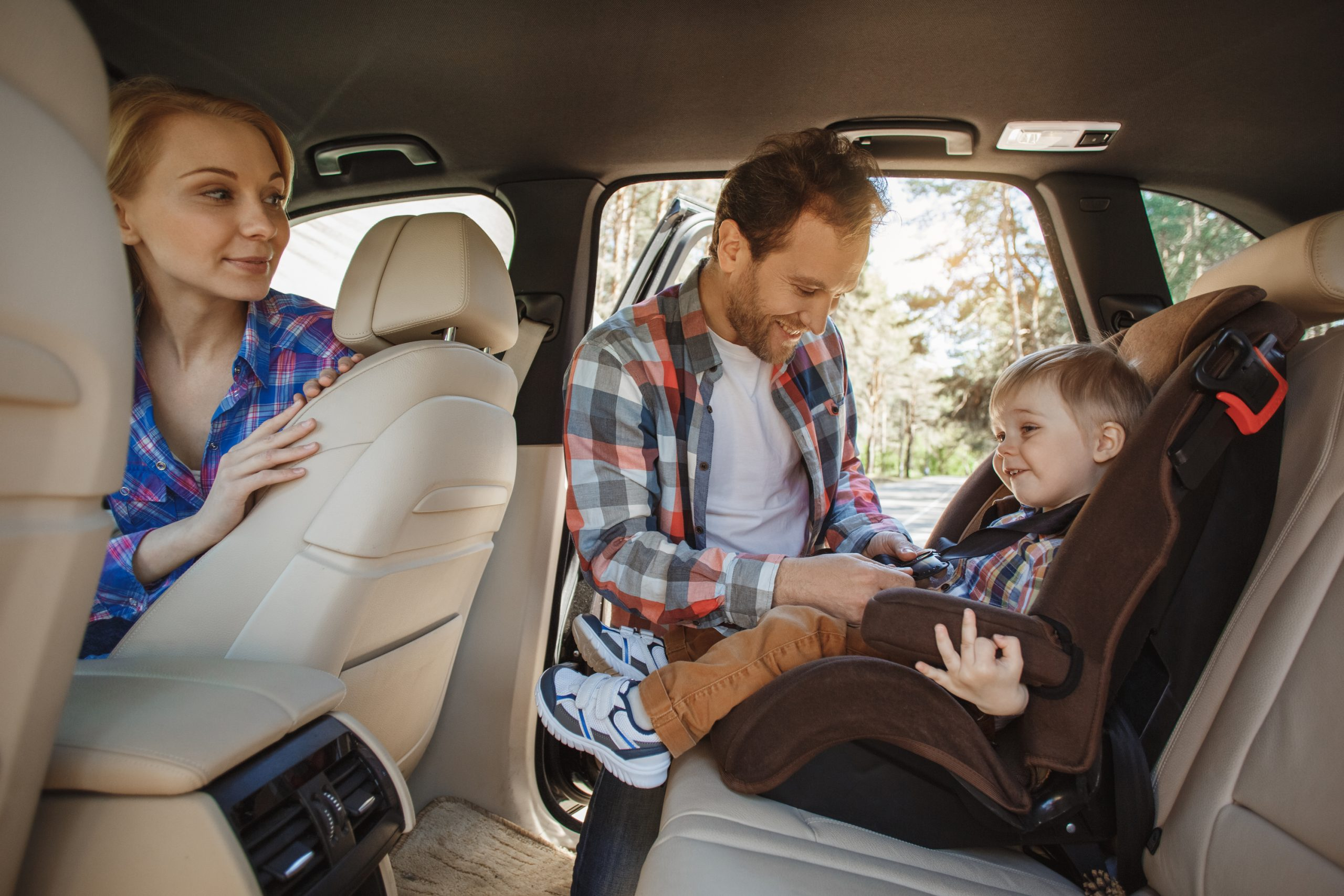 Parents buckling their child in a car seat. Another car hack for moms.