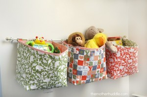 fabric baskets hung on a wall to store toys