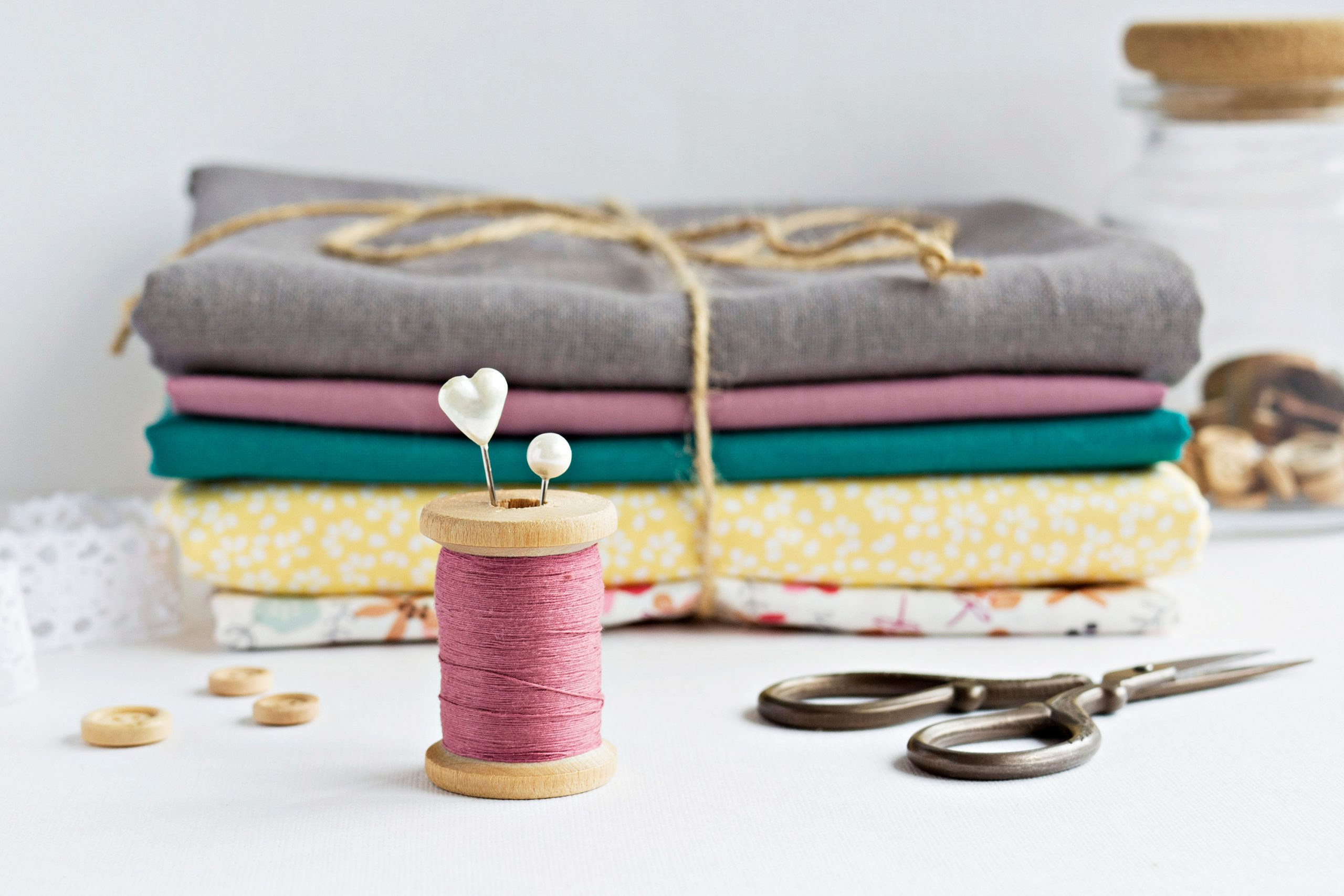 spool of thread with pile of fabric ready to be cut and sewn. Sewing tips and tricks.