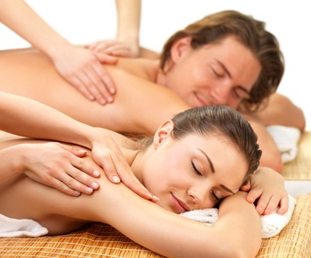Close up portrait of a romantic couple, on a spa holiday, having a back massage