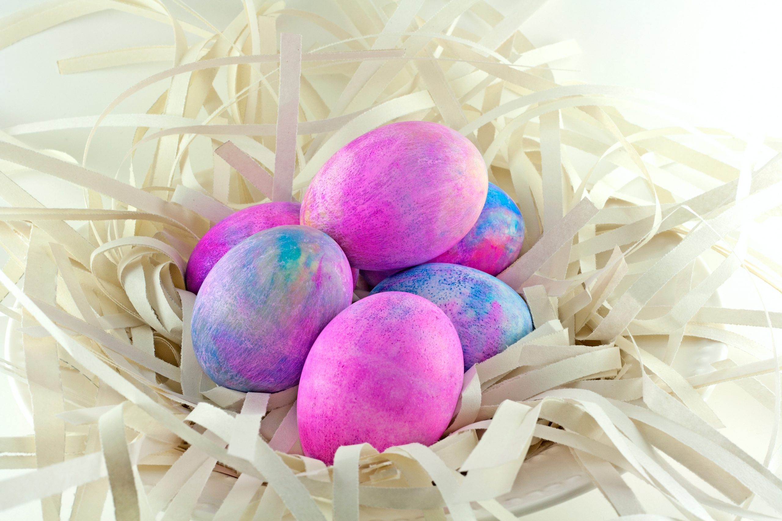 A basket full of shaving cream Easter eggs. The eggs have a mix of pink and blue. Shaving cream Easter eggs are very unique and artistic looking.