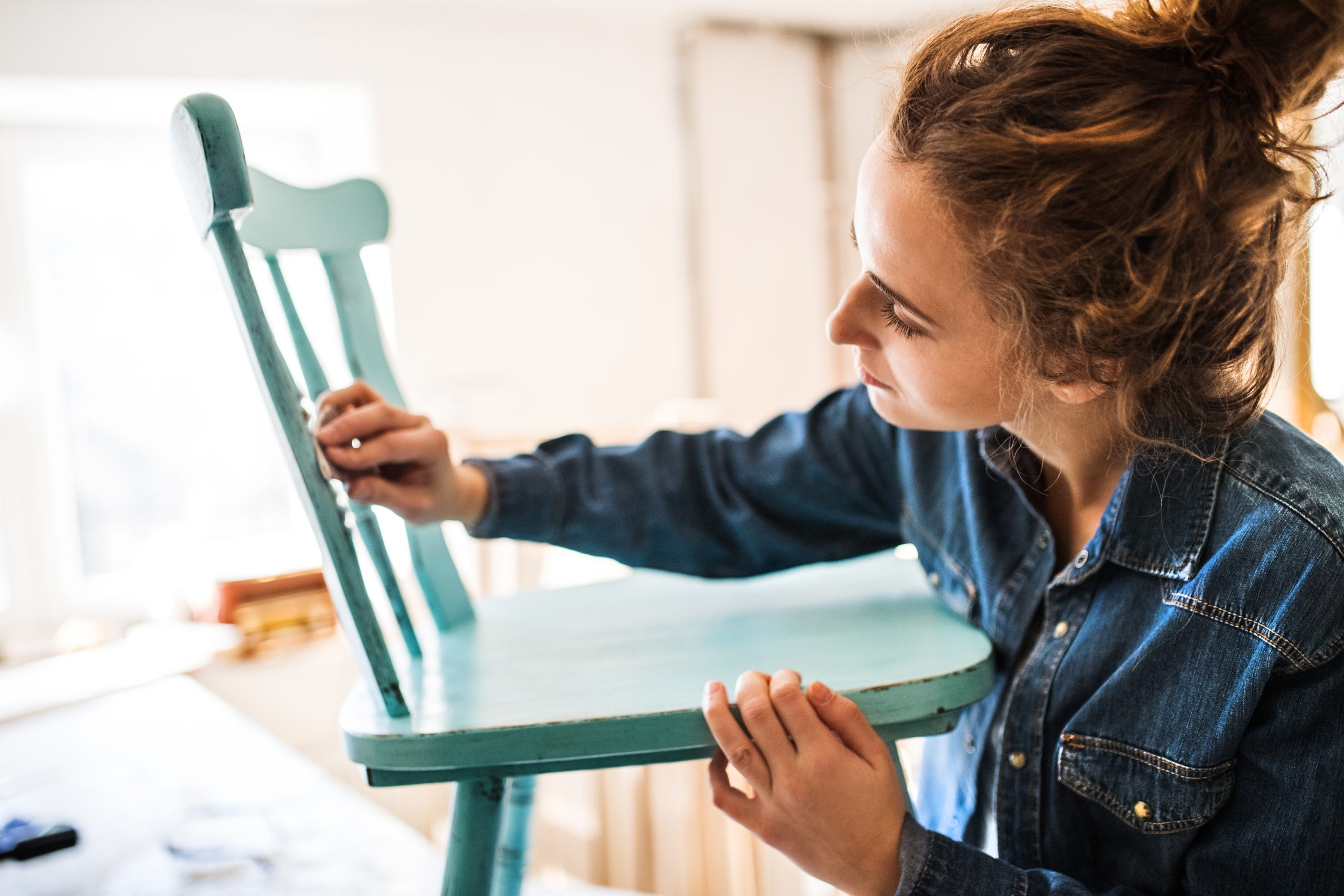 Sanding a wood chair. This is the first step for preparing to spray paint wood furniture.