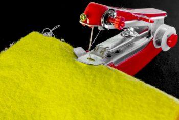 small red handheld sewing machine stitching on yellow fabric