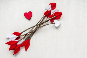 valentine twig crafts- twigs with red and white felt glued on to the ends to look like arrows
