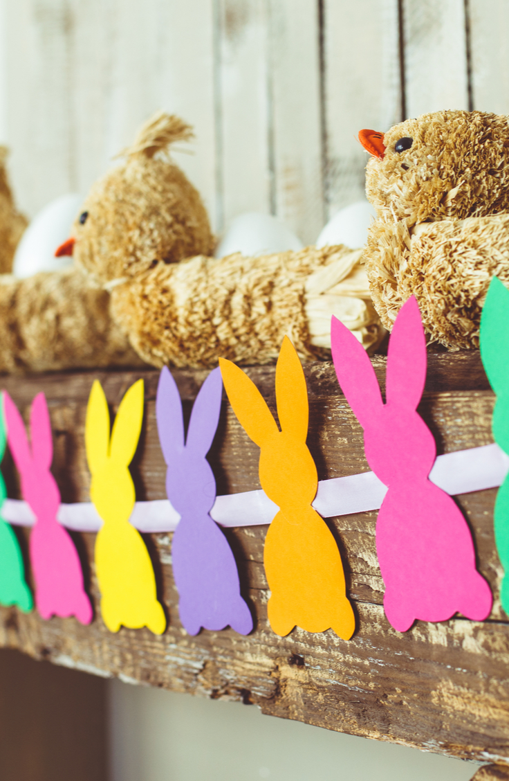Spring Decorating Ideas- A mantel banner made with paper bunnies in random colors of pink, orange, purple, yellow and green.
