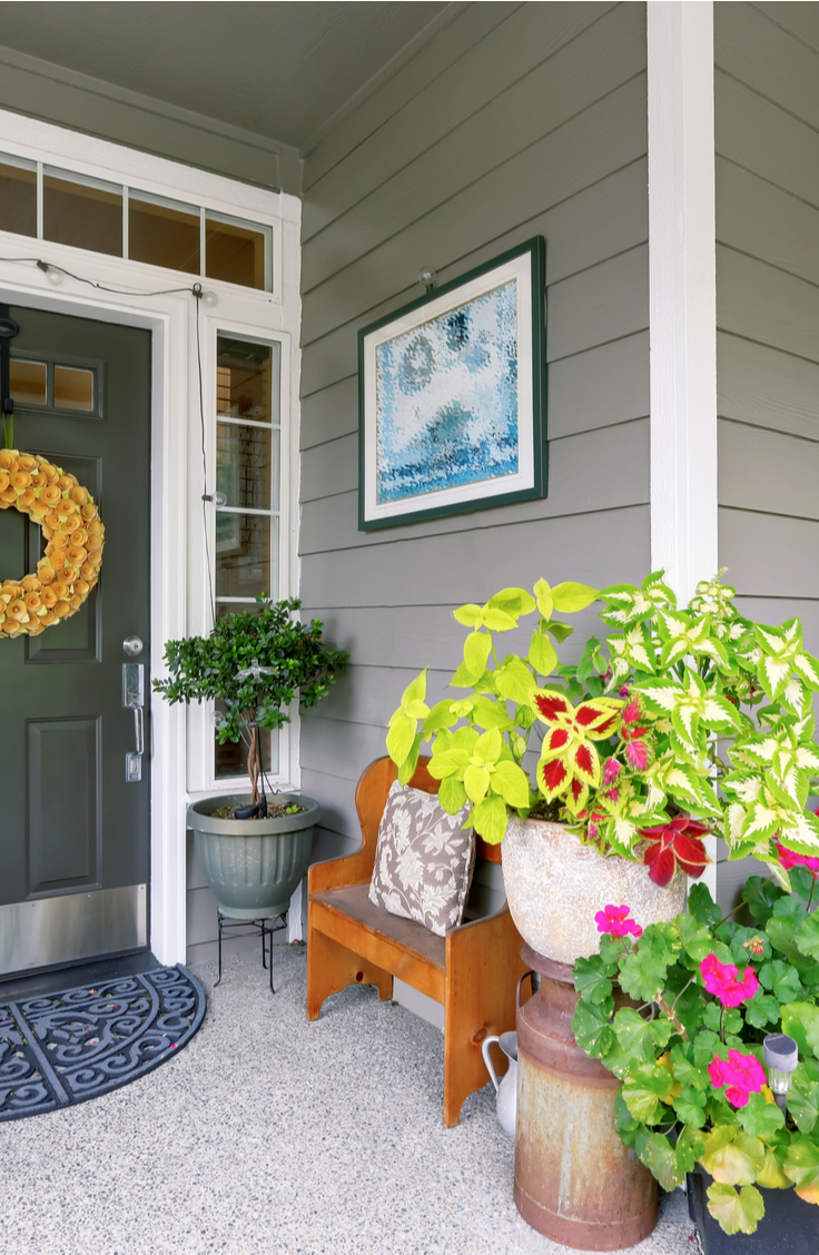 Spring Decorating Ideas- A front porch with spring decor. Gorgeous pink geraniums, coleus, milk can, wreath on front door.