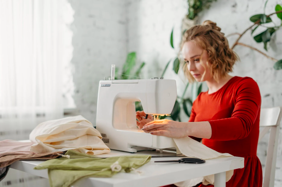 A woman in red stitching on a serger.